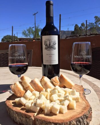 Bottle of Pies de Tierra wine, cheese board and two glasses of wine